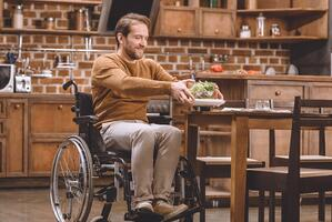 disabled man in wheelchair holding glass bowl of vegetable